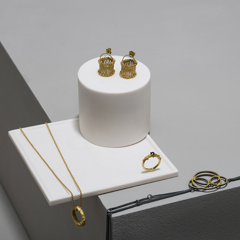 A selection of gold jewellery on grey and white plinths