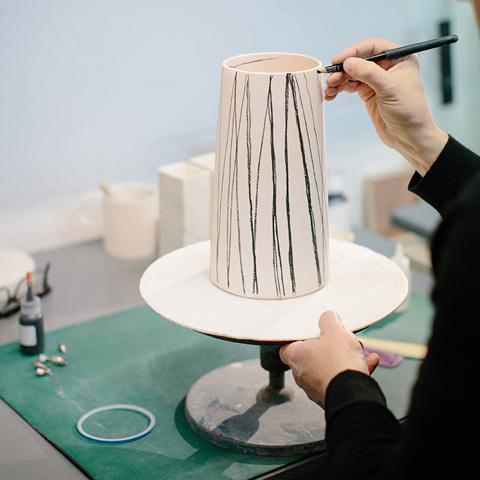 Myer Halliday illustrating white ceramic vase in studio