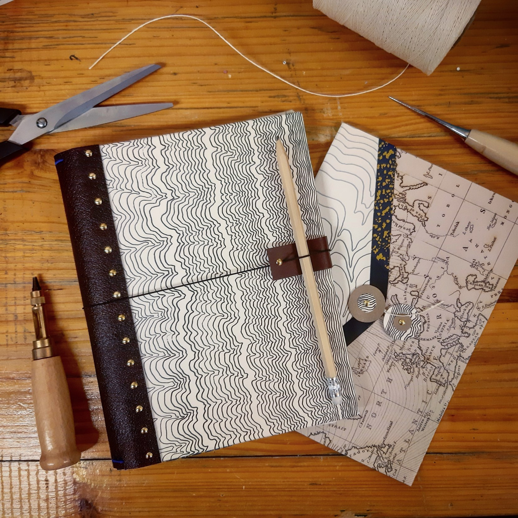 Two notebooks on a wooden table with thread, scissors and other bookbinding materials