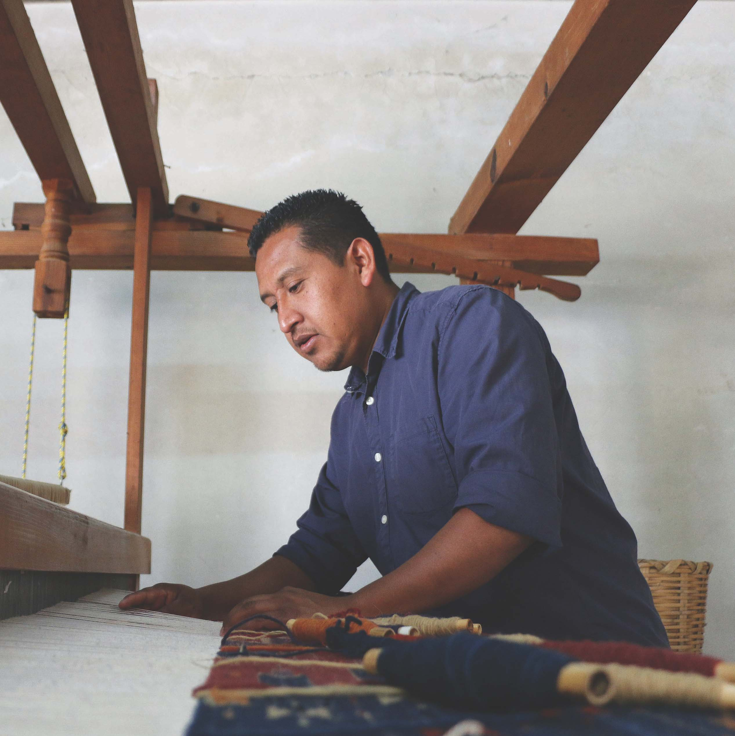 a person working on a tapestry in a weaving studio