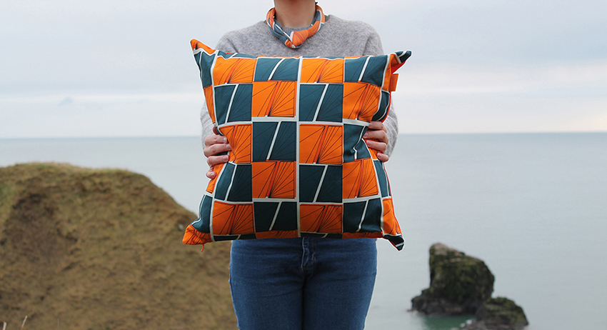 Model wearing patterned scarf holds patterned cushion in front of the sea