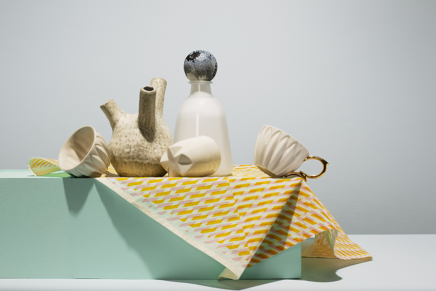 Collection of ceramics, glass and textiles sit on turquoise box